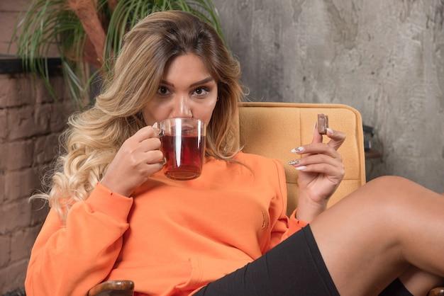 Młoda stylowa kobieta siedzi w fotelu, pijąc filiżankę herbaty.