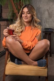 Młoda stylowa kobieta siedzi w fotelu trzymając filiżankę herbaty.