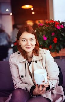 Młoda stylowa kobieta siedzi w kawiarni przy filiżance herbaty. jesienny czas. budapeszt, węgry, europa.