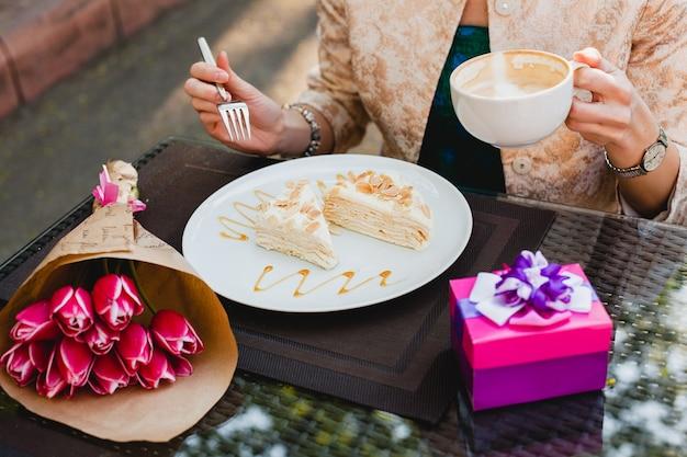 Młoda stylowa kobieta siedzi w kawiarni, trzymając kubek cappuccino i je smaczne ciasto,