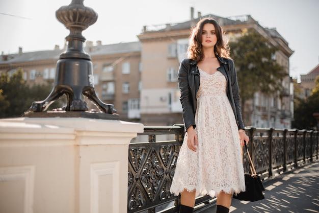 Młoda stylowa kobieta spaceru na ulicy w modnym stroju, trzymając torebkę, ubrana w czarną skórzaną kurtkę i białą koronkową sukienkę, styl wiosna jesień