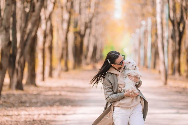 Młoda stylowa kobieta spaceru z białym psem