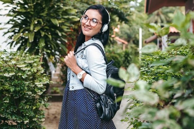 Młoda stylowa kobieta spaceru ze smartfonem, słuchanie muzyki na słuchawkach, wakacje