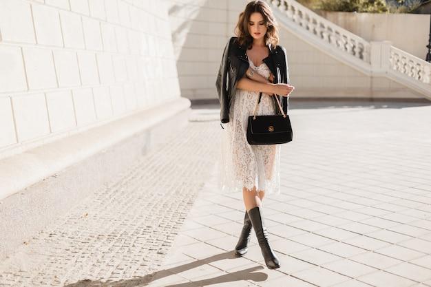 Młoda stylowa kobieta spacerująca po ulicy w modnym stroju, trzymając torebkę, ubrana w czarną skórzaną kurtkę i białą koronkową sukienkę, styl wiosenno-jesienny, pozowanie, wysokie skórzane buty