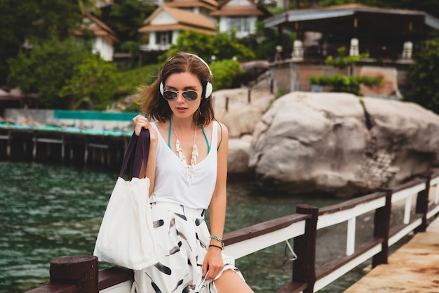 Młoda stylowa kobieta stojąca na molo, spacery, słuchanie muzyki na słuchawkach, letnia odzież, biała spódnica, torebka, lazurowa woda, tło krajobrazu, tropikalna laguna, wakacje, podróże po azji