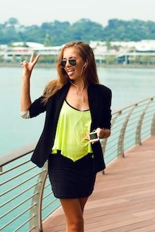 Młoda stylowa kobieta trzyma inteligentny telefon
