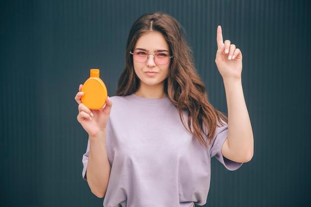 Młoda stylowa kobieta trzyma pomarańczową butelkę z filtrem przeciwsłonecznym spf ochrona twarzy