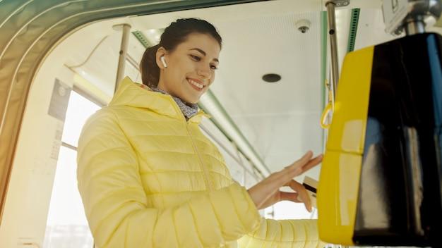 Młoda stylowa kobieta używa elektronicznego biletowego dziurkuje maszynę w transporcie publicznym. dziewczyna płaci bezkontaktowo kartą bankową za transport publiczny w tramwaju