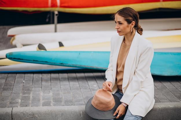 Młoda stylowa kobieta w białej kurtce w podróży