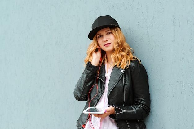 Młoda stylowa kobieta w czapce i skórzanej kurtce. hipster dziewczyna słuchania ulubionych piosenek audio w słuchawkach. dziewczyna pozuje nad szarości ścianą, kopii przestrzeń. ludzie, styl życia, koncepcja technologii