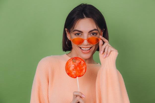 Młoda stylowa kobieta w dorywczo brzoskwiniowy sweter i pomarańczowe okulary na białym tle na zielonej oliwkowej ścianie z pomarańczowym lizakiem pozytywny uśmiech miejsca na kopię