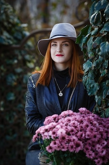 Młoda stylowa kobieta w kapeluszu spaceru na ulicy miasta wiosną
