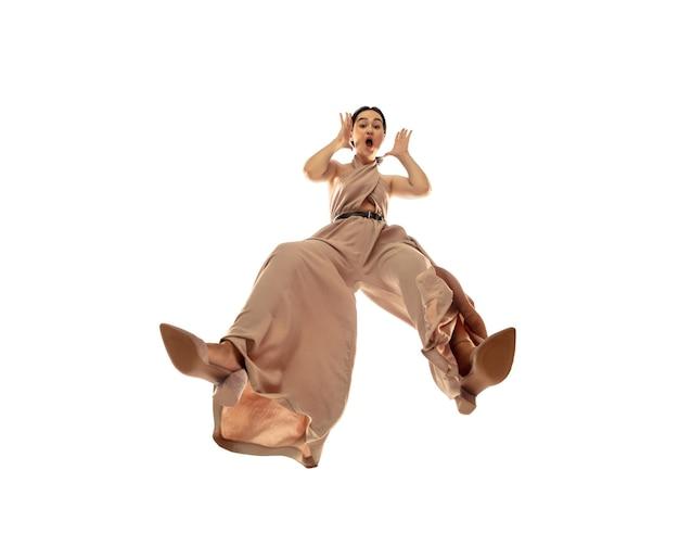 Młoda stylowa kobieta w nowoczesnym stroju w stylu ulicznym na białym tle, strzał od dołu