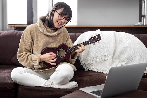 Młoda stylowa kobieta w okularach uczy się grać na ukulele. koncepcja edukacji online, edukacji domowej.