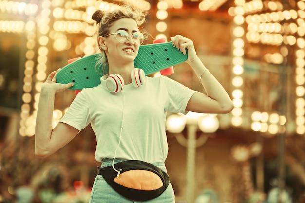 Młoda stylowa kobieta w stylowych ubraniach młodzieżowych z deskorolką na ramionach zabawy w parku rozrywki na tle oświetlenia.