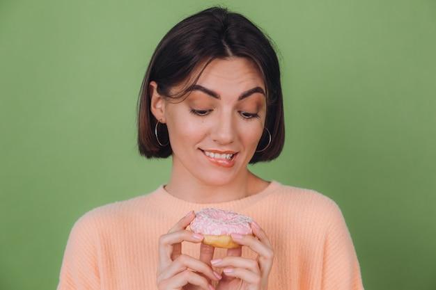 Młoda stylowa kobieta w swobodnym brzoskwiniowym swetrze i odizolowana na zielonej ścianie z oliwek patrzy na różowy pączek z głodową wargą