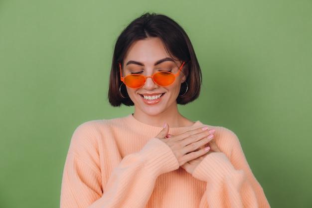 Młoda stylowa kobieta w swobodnym brzoskwiniowym swetrze i pomarańczowych okularach na zielonej ścianie z oliwek pozytywne trzymanie rąk złożonych na klatce piersiowej, miejsce na kopię serca