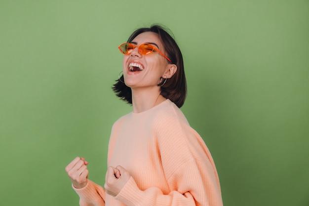 Młoda stylowa kobieta w swobodnym brzoskwiniowym swetrze i pomarańczowych okularach na zielonej ścianie z oliwek pozytywnie robi gest zwycięzcy zaciskając pięść kopia przestrzeń