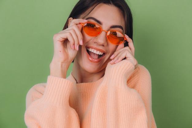 Młoda stylowa kobieta w swobodnym brzoskwiniowym swetrze i pomarańczowych okularach na zielonej ścianie z oliwek szczęśliwy pozytywny uśmiechnięty śmiech wokół przestrzeni kopii