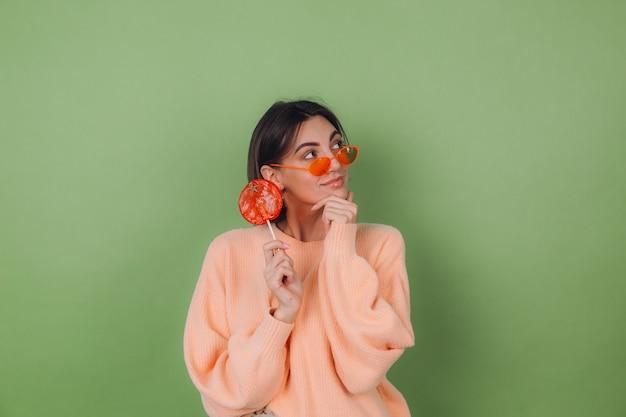 Młoda stylowa kobieta w swobodnym brzoskwiniowym swetrze i pomarańczowych okularach na zielonej ścianie z oliwek z pomarańczowym lizakiem