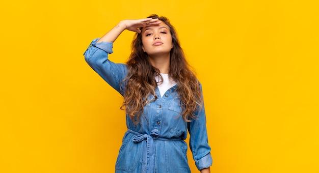 Młoda stylowa ładna kobieta na żółtym tle