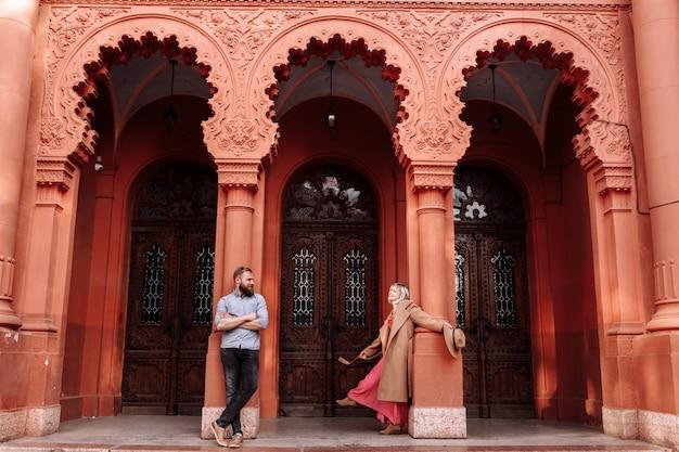 Młoda stylowa ładna para zakochanych hipsterów bawi się wiosną w mieście niedaleko zamku. młoda blond kobieta w czerwonej sukience i mężczyzna z brodą uśmiechają się na randkę