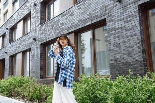 Młoda stylowa modelka pozuje na tle ulic miasta w nowej kolekcji letnich ubrań z kawą