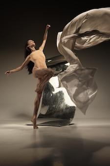 Młoda, stylowa nowoczesna tancerka baletowa na brązowej ścianie z lustrem
