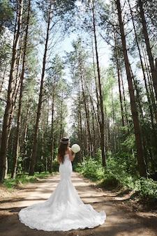 Młoda stylowa panna młoda z biżuterią w jej fryzurę w koronkowej sukni ślubnej, trzymając bukiet i pozowanie w lesie.