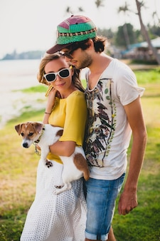 Młoda stylowa para zakochanych hipsterów trzyma psa w tropikalnym parku, uśmiecha się i bawi się podczas wakacji, nosi okulary przeciwsłoneczne, czapkę, żółtą i drukowaną koszulę, romans