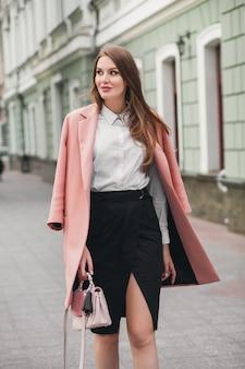 Młoda stylowa piękna kobieta idąca ulicą, ubrana w różowy płaszcz, torebkę, białą koszulę, czarną spódnicę, strój modowy, trend jesienny, uśmiechnięty szczęśliwy, akcesoria