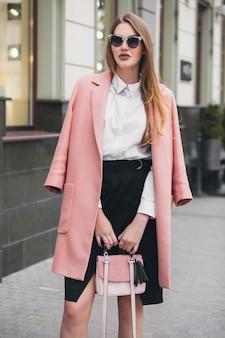 Młoda stylowa piękna kobieta idąca ulicą, ubrana w różowy płaszcz, torebkę, okulary przeciwsłoneczne, białą koszulę, czarną spódnicę, modny strój, jesienny trend, uśmiechnięty szczęśliwy, akcesoria