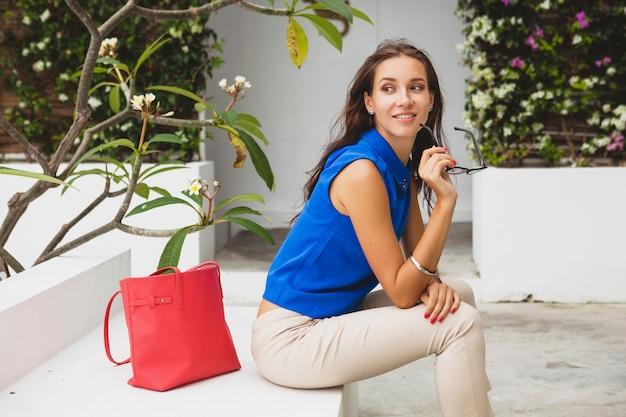 Młoda stylowa piękna kobieta, letni trend w modzie, niebieska bluzka, czerwona torba, okulary, tropikalna willa, wakacje, zalotna