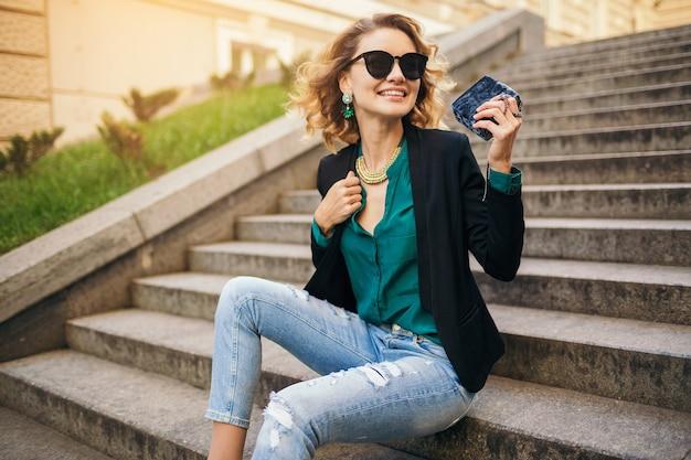 Młoda stylowa piękna kobieta siedzi na schodach na ulicy miasta, w dżinsach, czarnej kurtce, zielonej bluzce, okularach przeciwsłonecznych, trzymając torebkę, elegancki styl, letni trend w modzie, uśmiechając się