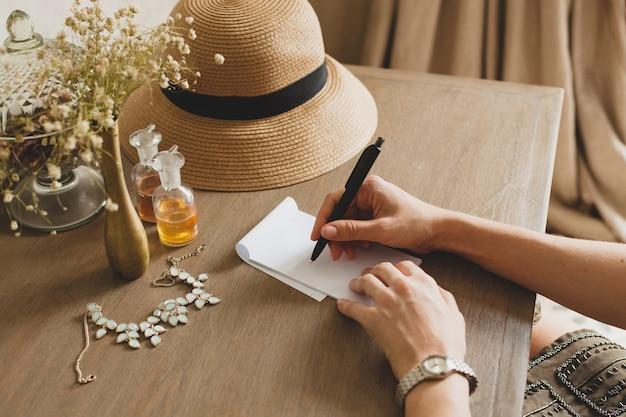 Młoda stylowa piękna kobieta siedzi przy stole w pokoju hotelowym ośrodka, pisze list, trzymając długopis, słomkowy kapelusz, styl vintage, zbliżenie rąk, szczegóły, akcesoria, dziennik podróży
