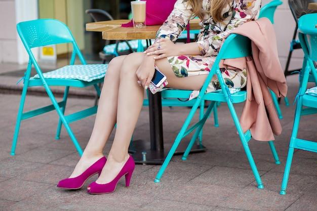Młoda stylowa piękna kobieta siedzi w kawiarni miejskiej na ulicy