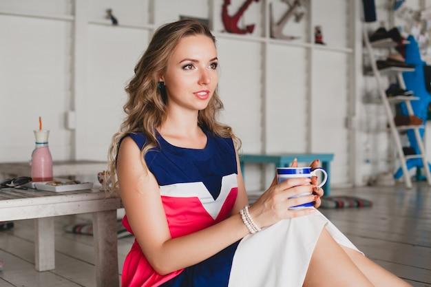Młoda stylowa piękna kobieta w kawiarni morskiej, picie gorącego cappuccino, styl kurortu, modny strój, uśmiechnięta, sukienka w morskich kolorach, siedząc na podłodze, wakacje, relaks
