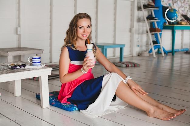Młoda stylowa piękna kobieta w kawiarni morskiej, pijąc koktajl koktajlowy, okulary przeciwsłoneczne, zalotne, styl kurortu, modny strój, uśmiechnięta, sukienka w morskich kolorach