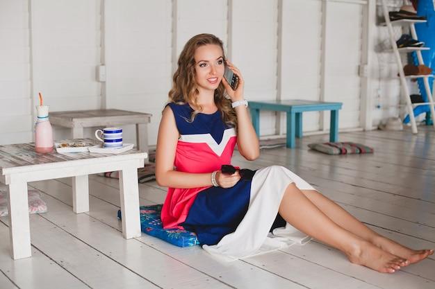 Młoda stylowa piękna kobieta w kawiarni morskiej, rozmawia przez telefon, styl kurortu, modny strój, uśmiechnięta, sukienka w marynistyczne kolory, siedzi na podłodze, wakacje, relaks