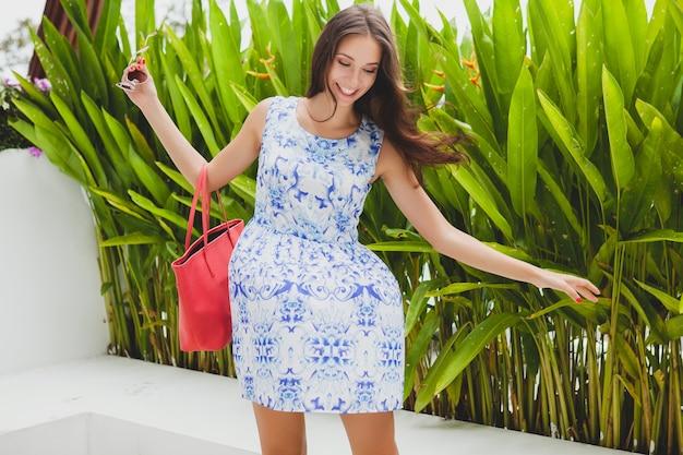 Młoda stylowa piękna kobieta w niebieskiej drukowanej sukience, czerwona torba, okulary przeciwsłoneczne, modny strój, modna odzież, uśmiechnięta, siedząca, lato, akcesoria