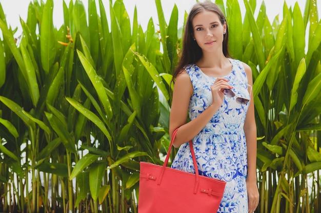 Młoda stylowa piękna kobieta w niebieskiej drukowanej sukience, czerwona torba, okulary przeciwsłoneczne, szczęśliwy nastrój, modny strój, modna odzież, uśmiechnięty, lato, akcesoria