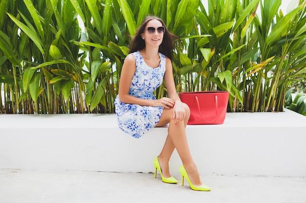 Młoda stylowa piękna kobieta w niebieskiej drukowanej sukience, czerwonej torbie, okularach przeciwsłonecznych, radosnym nastroju, modnym stroju, modnej odzieży, uśmiechnięta, siedząca, lato, żółte buty na wysokim obcasie, akcesoria