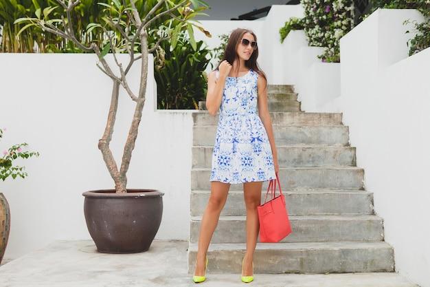 Młoda stylowa piękna kobieta w niebieskiej drukowanej sukience, czerwonej torbie, okularach przeciwsłonecznych, radosnym nastroju, modnym stroju, modnej odzieży, uśmiechnięta, stojąca, lato, żółte buty na wysokim obcasie, akcesoria