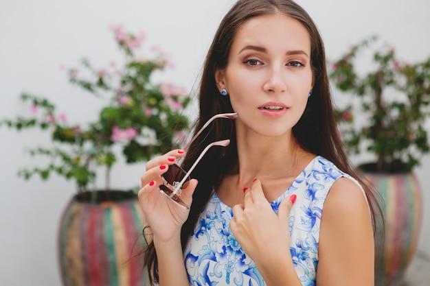 Młoda stylowa piękna kobieta w niebieskiej drukowanej sukience, okularach przeciwsłonecznych, radosnym nastroju, modnym stroju, modnej odzieży, uśmiechniętym, letnim, akcesoriach