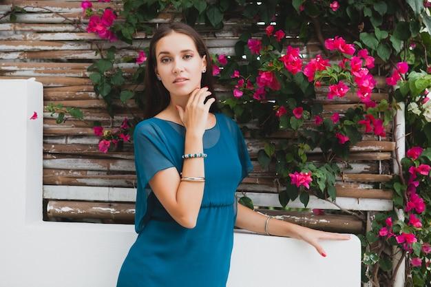 Młoda stylowa piękna kobieta w niebieskiej sukience, letni trend w modzie, wakacje, ogród, taras hotelu tropikalnego, uśmiechając się