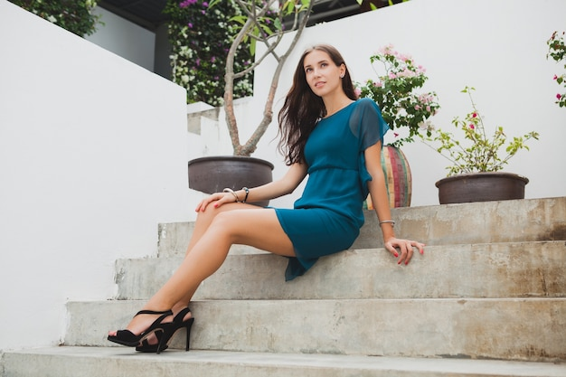 Młoda stylowa piękna kobieta w niebieskiej sukience, letni trend w modzie, wakacje, ogród, taras hotelu tropikalnego, uśmiechnięty, siedzący na schodach, długie nogi, buty, obcasy