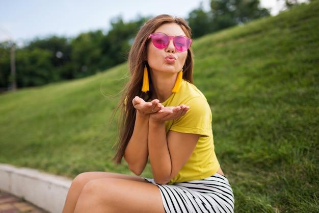 Młoda stylowa roześmiana kobieta bawi się w parku miejskim, uśmiechnięty wesoły nastrój, ubrana w żółty top, mini spódniczka w paski, różowe okulary przeciwsłoneczne, letni trend w modzie