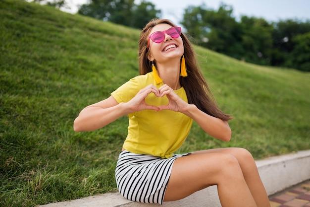 Młoda stylowa roześmiana kobieta bawiąca się w parku miejskim, uśmiechnięta wesoła nastrój, ubrana w żółty top, mini spódniczka w paski, różowe okulary przeciwsłoneczne, trend w modzie na lato, pokazujący znak serca