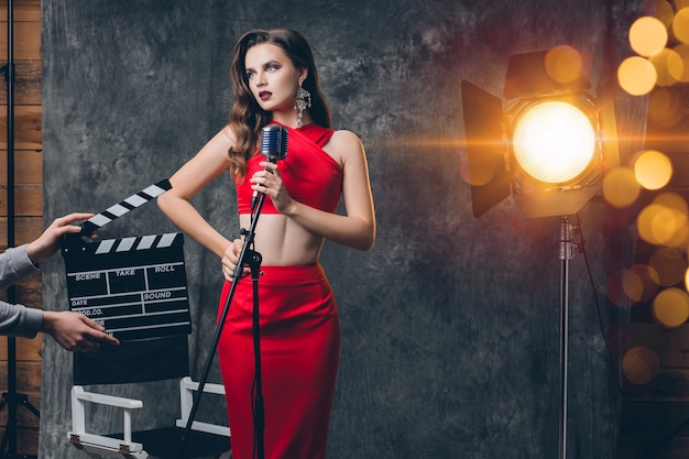 Młoda stylowa seksowna kobieta na kino za kulisami, świętuje, czerwona satynowa suknia wieczorowa, nastrój imprezowy, luksusowy styl