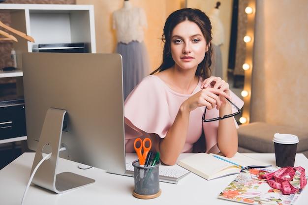 Młoda stylowa seksowna kobieta w różowej luksusowej sukience, letni trend, elegancki styl, projektant mody pracujący w biurze na komputerze